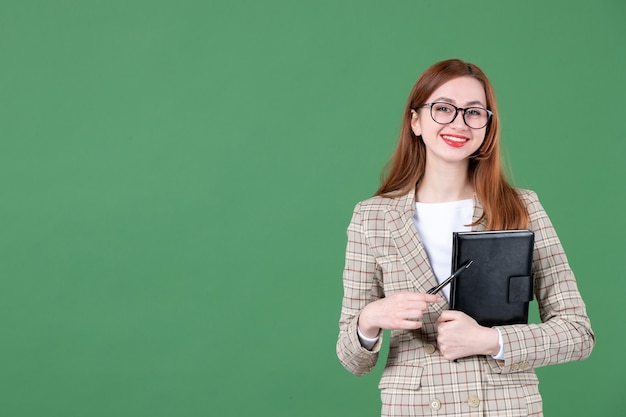 Portret van vrouwelijke leraar met notitieblok op groen
