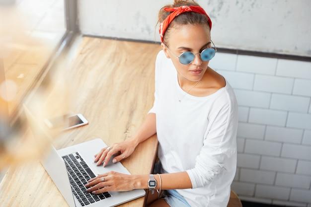 Portret van vrouwelijke manager werkt op businessplan op laptopcomputer, bladert informatie, kijkt bedachtzaam opzij, omringd met moderne elektronische gadgets. vrouwenredacteur controleert inhoud op website