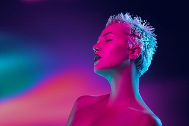 Portret van vrouwelijke mannequin in neonlicht op donker.
