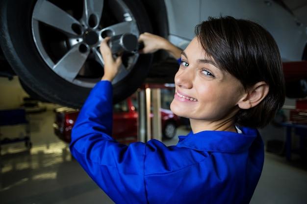 Portret van vrouwelijke monteur de vaststelling van een auto wiel met pneumatische moersleutel