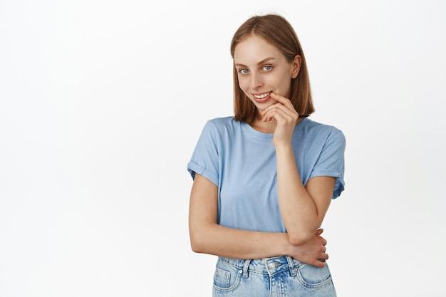 Portret van vrouwelijke mooie blonde vrouw met blauwe ogen, koket naar voren starend, flirterig glimlachen, heeft een idee, interessante gedachte, staande tegen de witte muur.