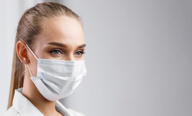 Portret van vrouwelijke onderzoeker met medisch masker en exemplaarruimte