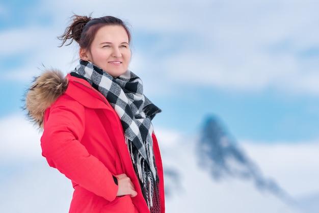 Portret van vrouwelijke reiziger gekleed in rode winter winddichte jas, zwart-witte sjaal om de nek. mysterieuze mooie jonge vrouw op de achtergrond van bergen en blauwe lucht met witte wolken.