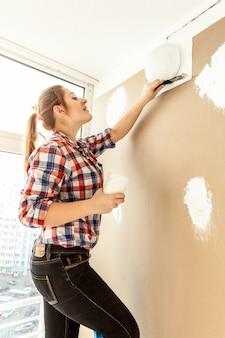 Portret van vrouwelijke schilder die gipskartonnen muur pleistert