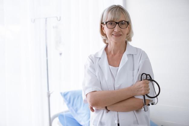 Portret van vrouwelijke senior arts zitten in medische kantoor