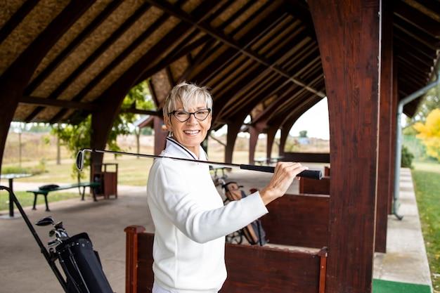 Portret van vrouwelijke senior golfer die op de golfbaan staat en glimlacht.