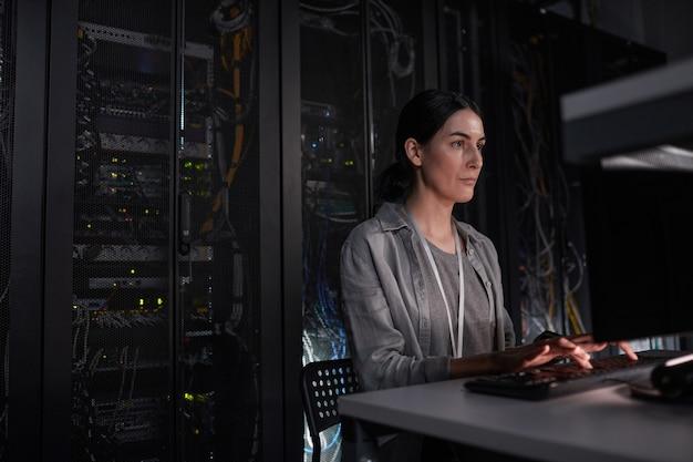 Portret van vrouwelijke serveringenieur die laptop gebruikt terwijl ze in een donkere it-kamer zit, kopieer ruimte