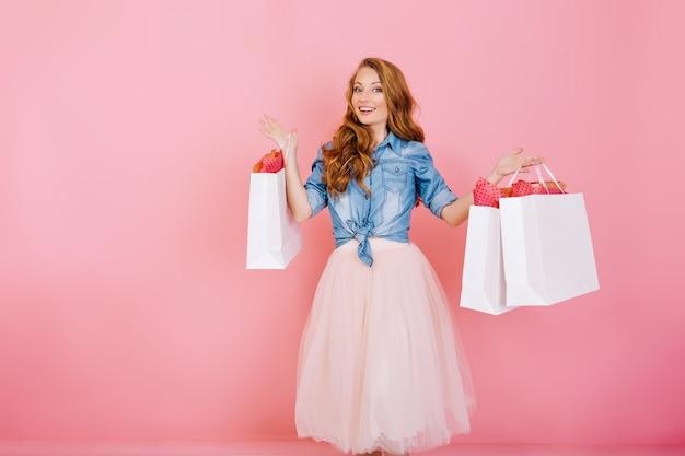 Portret van vrouwelijke shopaholic met papieren zakken van favoriete winkels en glimlachen, geïsoleerd op roze achtergrond. aantrekkelijke jonge vrouw met krullend haar komt terug van het winkelen met pakketten