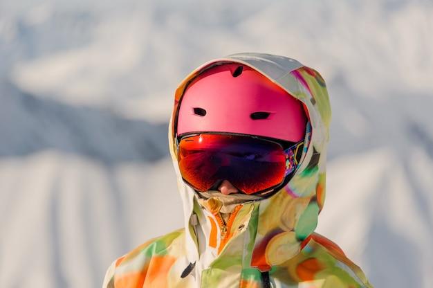 Portret van vrouwelijke snowboarder in roze sporthelm en heldere kleurrijke sportkleding