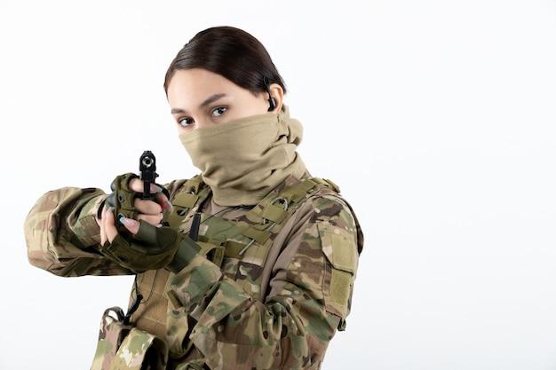 Portret van vrouwelijke soldaat met pistool in camouflage witte muur