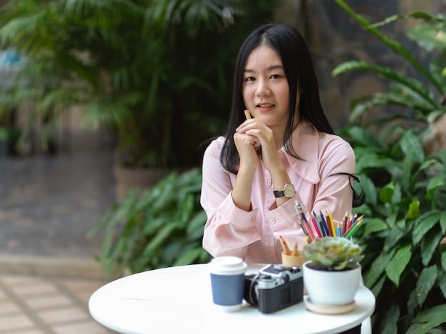 Portret van vrouwelijke student glimlachen naar de camera tijdens het toewijzen bedoeld in café