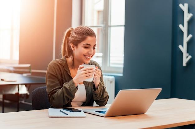 Portret van vrouwelijke student zit in de bibliotheek met een laptopcomputer.