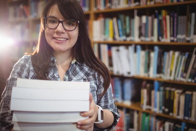 Portret van vrouwelijke studenten die een stapel van boeken in bibliotheek houden