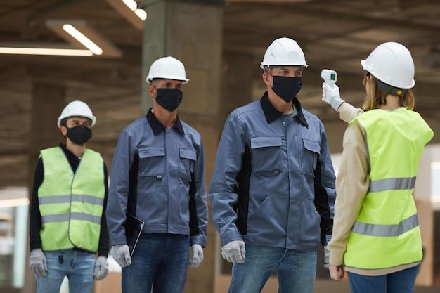 Portret van vrouwelijke supervisor die temperatuur van arbeiders met contactloze thermometer meet op bouwplaats, veiligheidsmaatregelen van het coronavirus