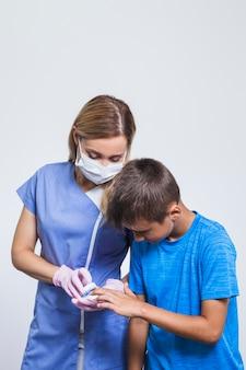 Portret van vrouwelijke tandarts en jongen die tandenmodel bekijken