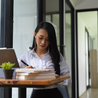 Portret van vrouwelijke te concentreren op haar werk met boeken, laptop en leveringen op werktafel in kantoorruimte