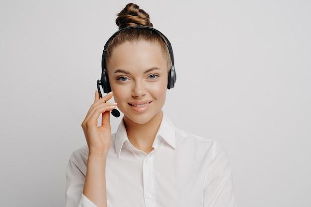 Portret van vrouwelijke technische ondersteuningsmedewerker in klassieke outfit met zwarte headset die de reden van de problemen uitlegt en een oplossing geeft aan de beller terwijl ze geïsoleerd naast een lichte muur staat en naar de camera kijkt