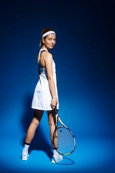 Portret van vrouwelijke tennisspeler met racket het stellen in studio