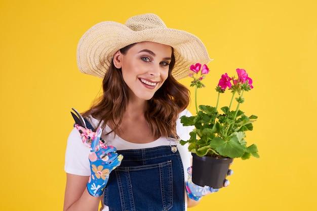 Portret van vrouwelijke tuinman die bloem in bloempot snoeit
