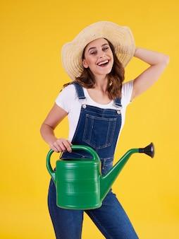 Portret van vrouwelijke tuinman met gieter in studio shot