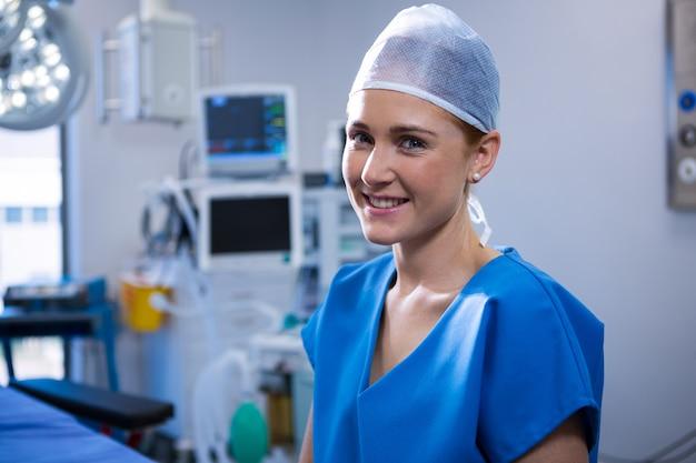 Portret van vrouwelijke verpleegster die in verrichtingstheater glimlachen