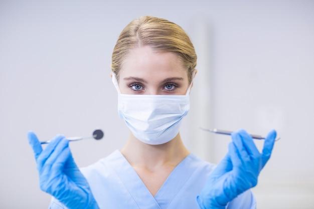Portret van vrouwelijke verpleegster die tandhulpmiddelen houdt