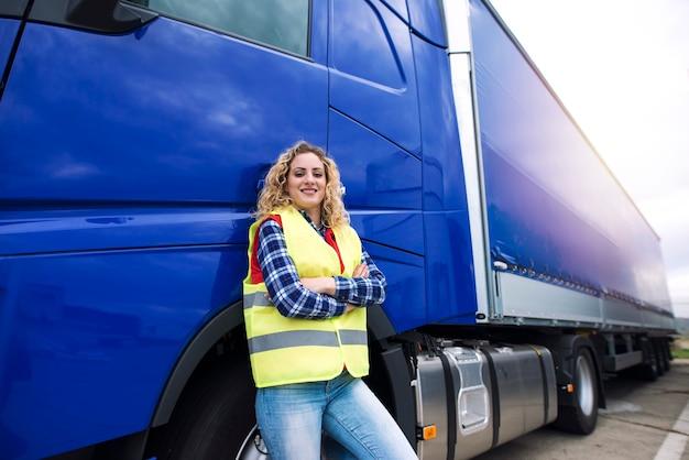 Portret van vrouwelijke vrachtwagenchauffeur die zich door vrachtwagenvoertuig bevindt.