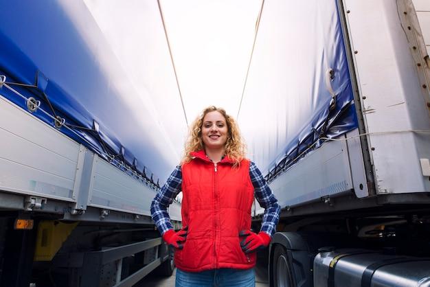 Portret van vrouwelijke vrachtwagenchauffeur die zich trots tussen aanhangwagens en vrachtwagenvoertuig bevindt.