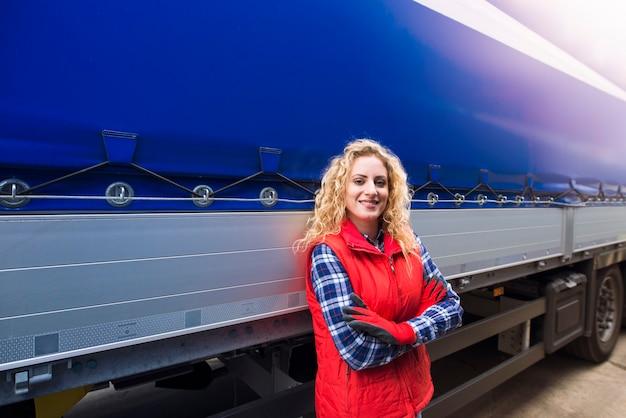 Portret van vrouwelijke vrachtwagenchauffeur met gekruiste arm trots permanent door haar vrachtwagen voertuig klaar voor transport service.