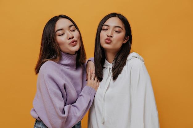 Portret van vrouwelijke vriend in truien blaast kusjes op geïsoleerd