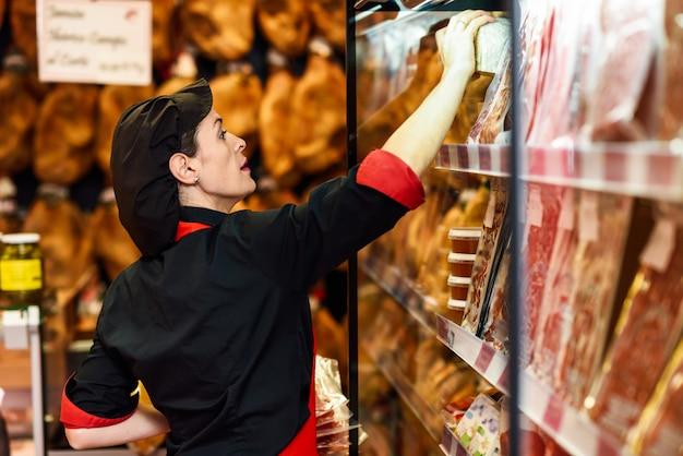 Portret van vrouwelijke werknemer die producten in slagerswinkel nemen