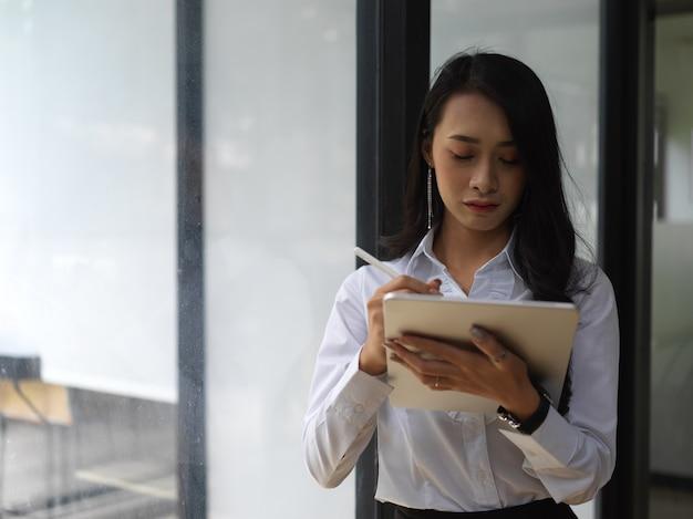 Portret van vrouwelijke werknemer met behulp van digitale tablet terwijl staande in de vergaderzaal van de glazen wand