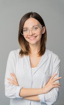 Portret van vrouwelijke wetenschapper die zich met haar gekruiste wapens bevindt