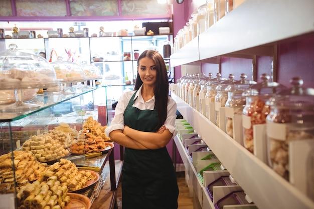 Portret van vrouwelijke winkelier die zich bij turkse zoetigheidsteller bevindt
