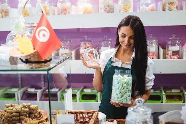 Portret van vrouwelijke winkelier met pot turkse snoepjes aan balie