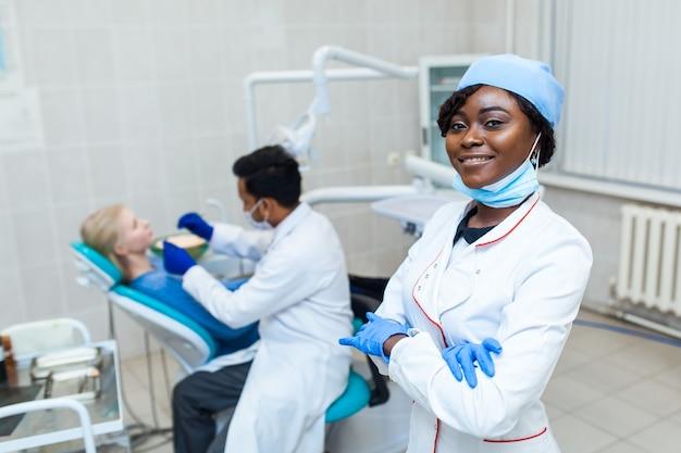 Portret van vrouwelijke zwarte tandarts in tandartspraktijk. ze staat op haar kantoor en ze heeft een mooie glimlach. moderne medische apparatuur