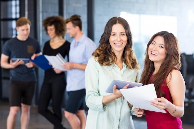 Portret van vrouwen die digitale tablet houden en glimlachen terwijl collega's die zich erachter in bureau bevinden