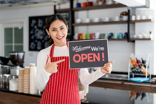 Portret van vrouwenserveerster die zich bij haar koffiewinkelpoort bevindt met het tonen van open uithangbord