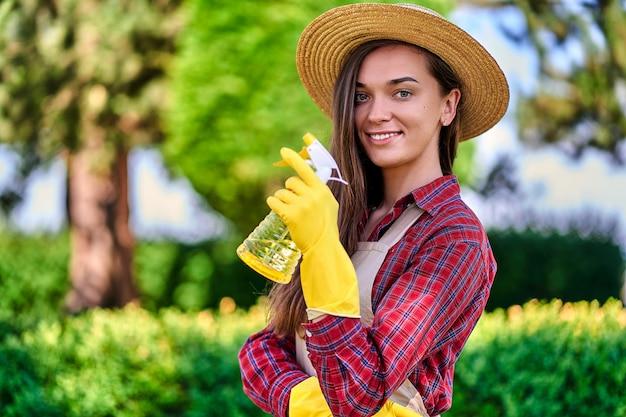 Portret van vrouwentuinman met nevelfles voor het water geven van installaties in groene tuin