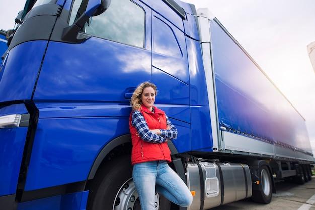 Portret van vrouwenvrachtwagenchauffeur die zich door het vrachtwagenvoertuig bevinden.