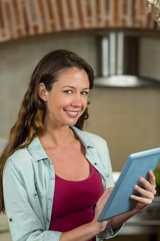Portret van vrouwenzitting op worktop en het gebruiken van tablet in keuken
