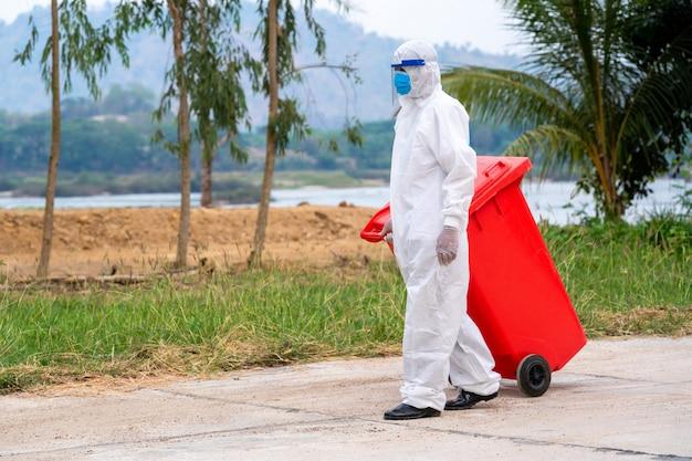 Portret van vuilnisman in beschermende kleding van hazmat ppe, draagt medisch rubber met trucklaadafval en prullenbak, coronavirus disease 2019, coronavirus is een wereldwijde noodsituatie geworden.