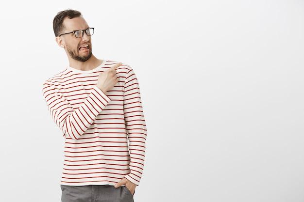 Portret van walgen volwassen man met bril, naar links buigend terwijl hij wijst en met ongenoegen naar de rechterbovenhoek kijkt