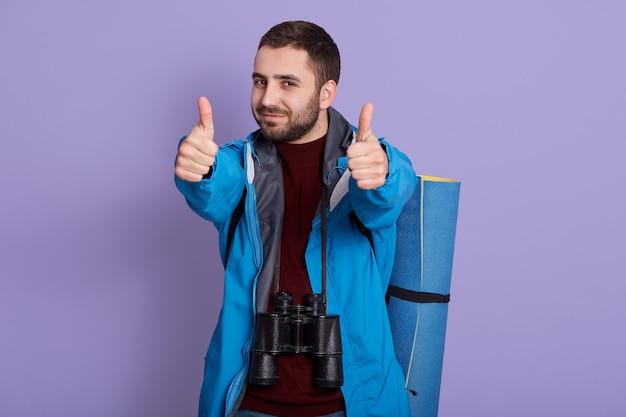 Portret van wandelaar met rugzak poseren geïsoleerd op lila achtergrond
