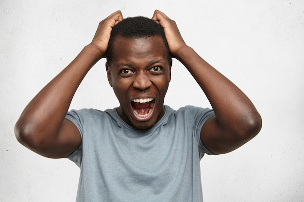 Portret van wanhopige geërgerde zwarte man schreeuwen van woede en woede scheurt zijn haar terwijl hij woedend en boos op iets voelt. negatieve gezichtsuitdrukkingen, emoties en gevoelens