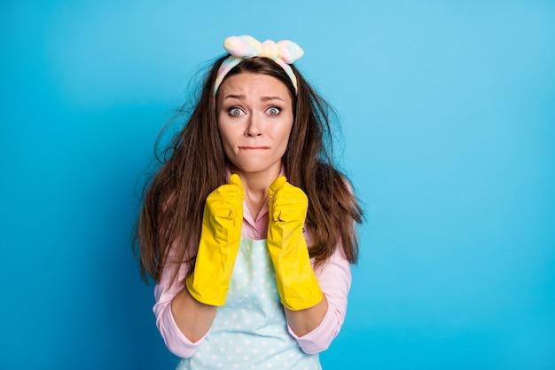 Portret van wanhopige meid die het huis schoonmaakt, zorgwekkend