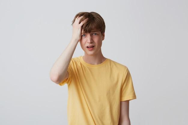Portret van wanhopige ongelukkige jonge man met hand op hoofd