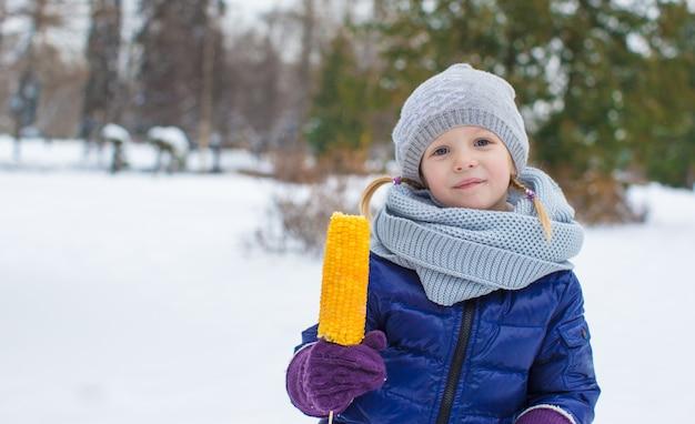 Portret van weinig aanbiddelijk meisje in de winterhoed in openlucht
