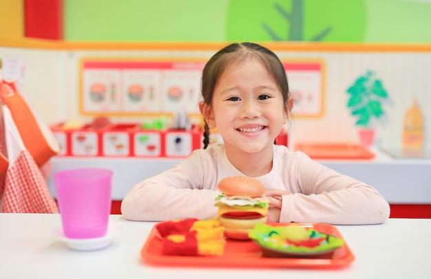 Portret van weinig aziatisch jong geitjemeisje die in snel voedselwinkel spelen.