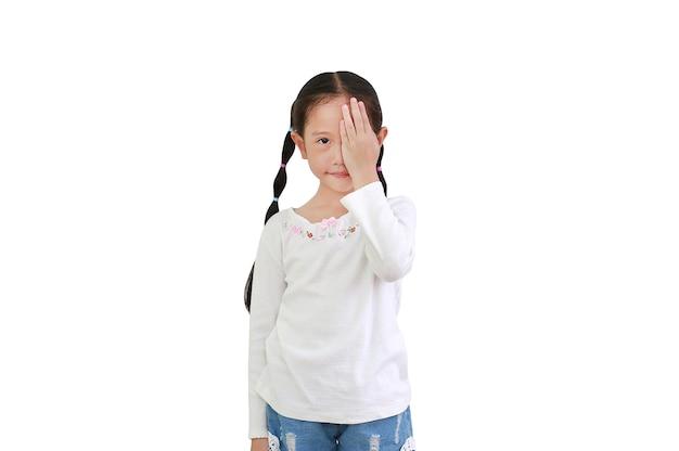 Portret van weinig aziatisch kindmeisje dat één oog met hand sluit dat op witte achtergrond wordt geïsoleerd die camera kijkt.